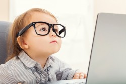 Smart little toddler girl wearing big glasses while using her laptop